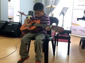 A young boy plays a guitar
