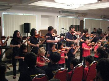 A group of violin players making music at our Kuala Belait recital