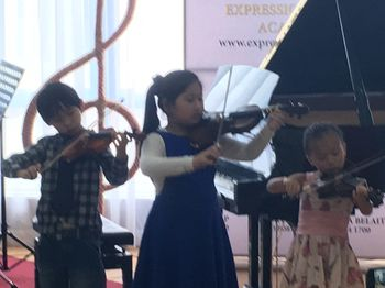 3 young children playing Violins during our Kuala Belait recital
